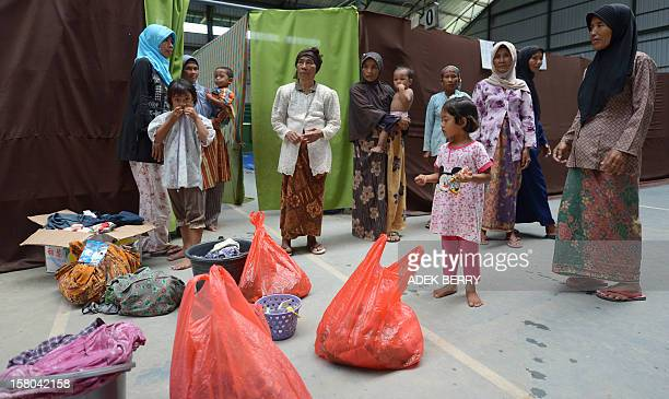 This picture taken on November 30 shows women and children standing with their belongings at a temporary shelter for Muslim Shiites in Sampang....