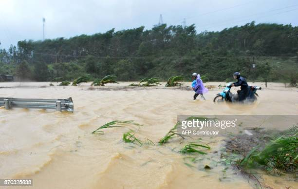 This picture taken on November 4, 2017 shows people walking through floodwaters on a highway in the central province of Dak Lak brought by Typhoon...
