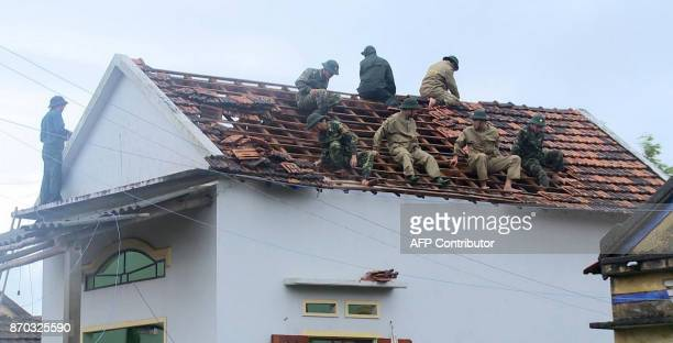 This picture taken on November 4 2017 shows soldiers fixing the damaged roof of a local home in the central province of Quang Ngai after Typhoon...