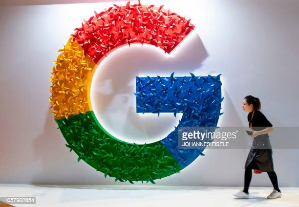 TOPSHOT This picture taken on November 5 2018 shows a woman passing a booth of Google at the first China International Import Expo in Shanghai on