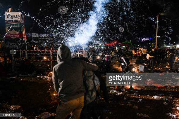 This picture taken on November 5 2019 shows a couple running for cover as fireworks explode after a hotair balloon attached with fireworks was...