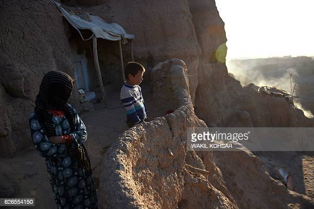 This picture taken on November 6 2016 shows Afghan Hazara children stand in front of the cave where they live with their family in Bamiyan province...