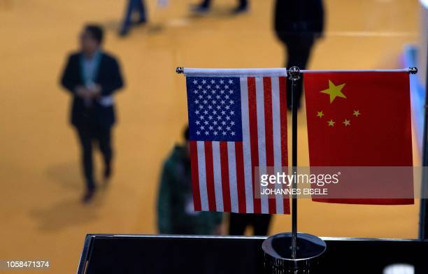 This picture taken on November 6 2018 shows a Chinese and US flag at a booth during the first China International Import Expo in Shanghai There is a...