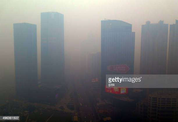 This picture taken on November 8 2015 shows a residential block covered in smog in Shenyang China's Liaoning province A swathe of China was blanketed...