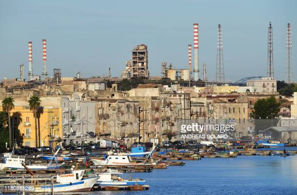 This picture taken on November 8 shows a general view of the ArcelorMittal Italia steel plant seen past the Tamburi residential district in Taranto...