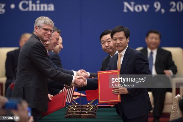 This picture taken on November 9 2017 shows Lei Jun the CEO of Chinese smartphone maker Xiaomi shaking hands with Qualcomm CEO Steven Mollenkopf...