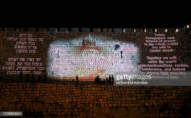 This picture taken on November 9, 2020 shows the walls of the old city of Jerusalem lit with messages of hope and images of synagogues, mosques,...