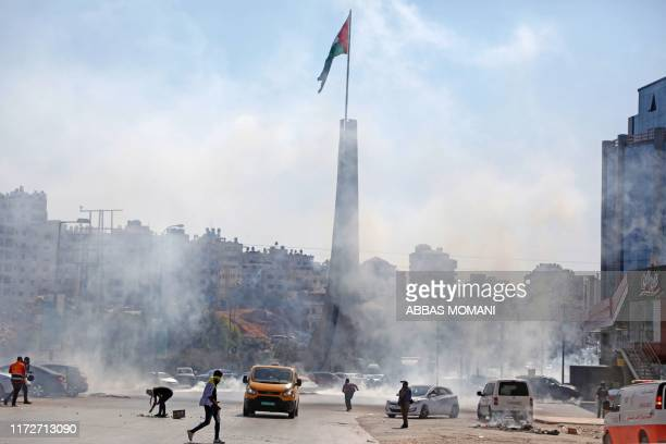 This picture taken on October 1, 2019 shows tear gas fumes erupting at the scene of clashes between Palestinina protesters and Israeli security...