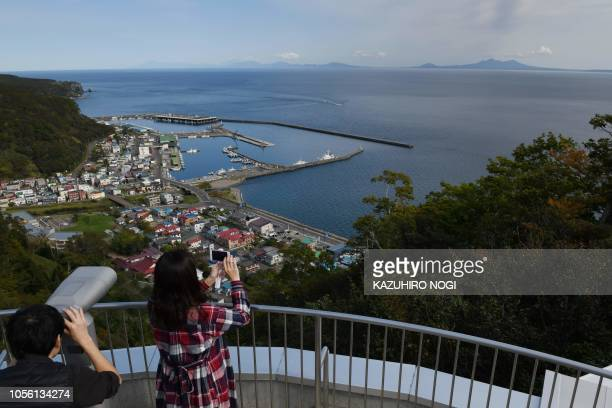 This picture taken on October 10 2018 shows tourists looking at the island of Kunashiri from the Rausu Kunashiri Observatory Deck in Rausu a town...