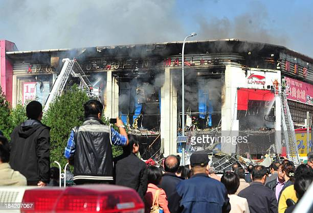 This picture taken on October 11 2013 shows local residents gathering outside a shopping mall that caught fire in the early morning in the...