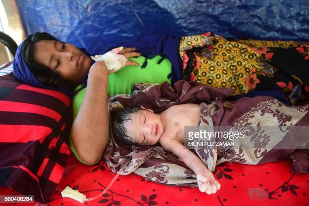 This picture taken on October 11 2017 shows pregnant Rohingya woman Hasina Aktar lying in bed with her newborn baby Mohammed Jubayed at a medical...