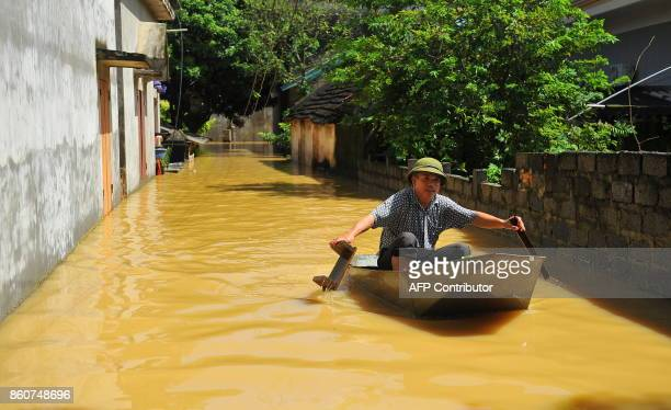TOPSHOT This picture taken on October 12 2017 shows a villager using a boat to cross a flooded alley at a village in the northern province of Ninh...
