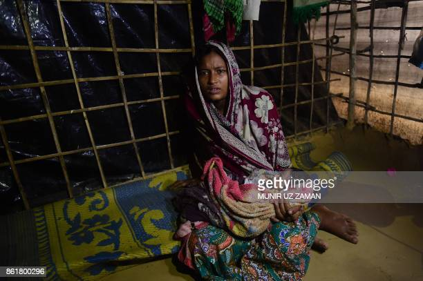 This picture taken on October 12 2017 shows Rohingya woman Hasina Aktar with her newborn baby Mohammed Jubayed at their house in Kutupalong refugee...