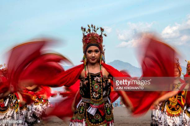 This picture taken on October 12 2019 shows a traditional dancer performing during the Gandrung Sewu festival on Boom beach in Banyuwangi East Java...