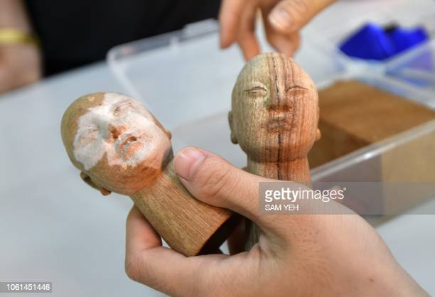 This picture taken on October 13 2018 shows a student of Chen Hsihuang an 87yearold Taiwanese glove puppeteer showing two puppet heads during a...