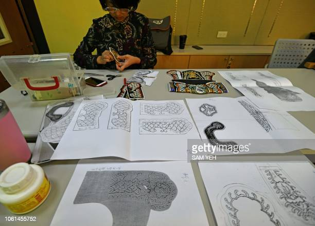 This picture taken on October 13 2018 shows a student of Chen Hsihuang an 87yearold Taiwanese glove puppeteer making embroidery of a puppet's clothes...