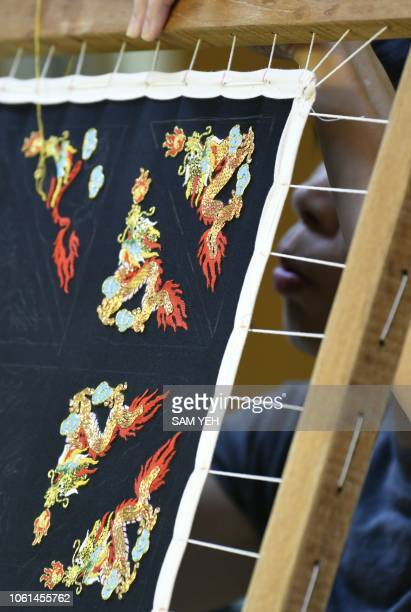 This picture taken on October 13 2018 shows a student of Chen Hsihuang an 87yearold Taiwanese glove puppeteer making embroidery for a glove puppet at...