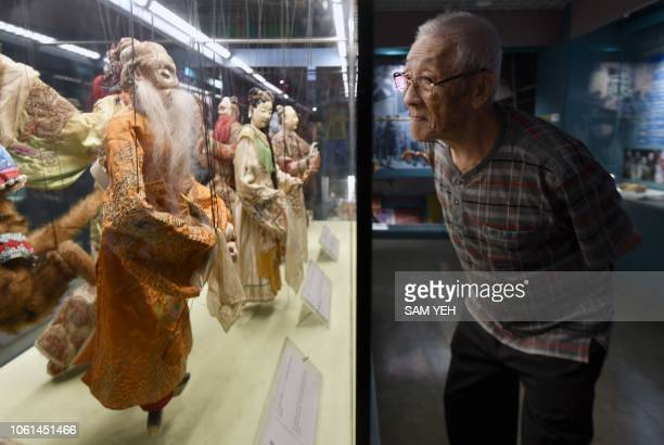 This picture taken on October 13 2018 shows Chen Hsihuang an 87yearold Taiwanese glove puppeteer looking at puppets at the Puppetry Art Center in...