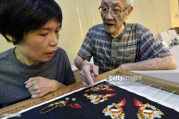 This picture taken on October 13 2018 shows Chen Hsihuang an 87yearold Taiwanese glove puppeteer teaching a student how to make embroidery at...