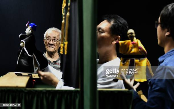 This picture taken on October 13 2018 shows Chen Hsihuang an 87yearold Taiwanese glove puppeteer standing next to a puppet show being performed by...