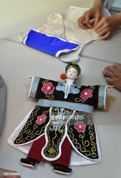 This picture taken on October 13 2018 shows students of Chen Hsihuang an 87yearold Taiwanese glove puppeteer learning how to make clothes for puppets...