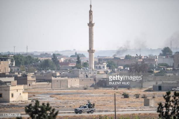 This picture taken on October 13, 2019 from the Turkish city of Akcakale shows Turkey-backed Syrian National Army fighters driving a pickup truck...