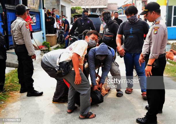 This picture taken on October 13 2019 shows a special Indonesian police team apprehending a suspected militant outside a home in Bekasi West Java...