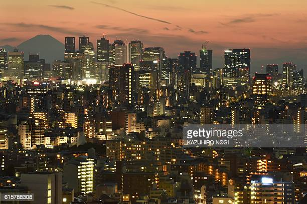This picture taken on October 15 2016 shows Japan's highest mountain Mount Fuji at 3776 meters seen behind skyscrapers in Tokyo's Shinjuku area...