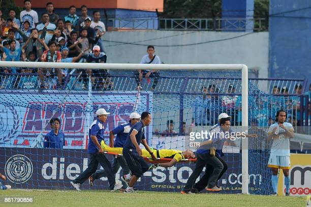 TOPSHOT This picture taken on October 15 2017 shows goalkeeper Choirul Huda of hometown club Persela in East Java being rushed away on a stretcher...