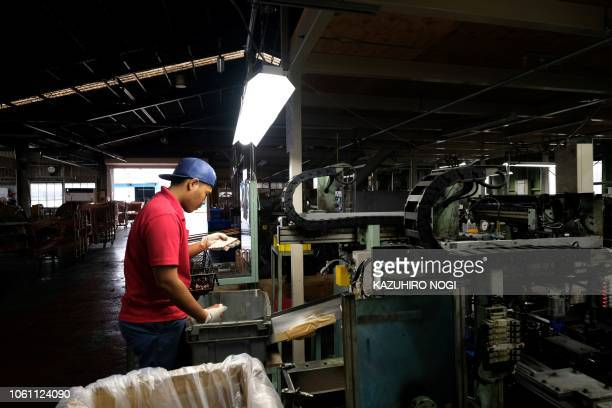 This picture taken on October 16 2018 shows an Indonesian worker processing copper pipes at a Nakamoto Mfg factory in Oizumi Gunma prefecture Ageing...