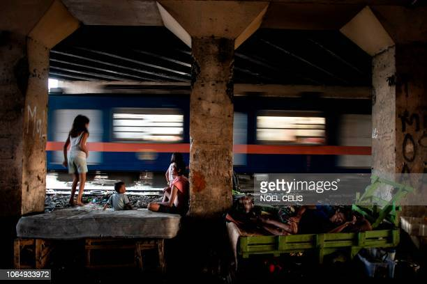 This picture taken on October 17 2018 shows a family living along a train track in Manila Scores of commuters in the city of about 12 million are...
