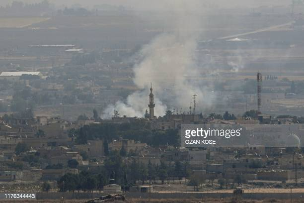 This picture taken on October 17 2019 from the Turkish side of the border with Syria in the Ceylanpinar district city of Sanliurfa shows smoke rising...