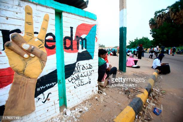 This picture taken on October 17 2019 shows Sudanese demonstrators gathering for a vigil outside the entrance of the former Nile Street sitin in the...