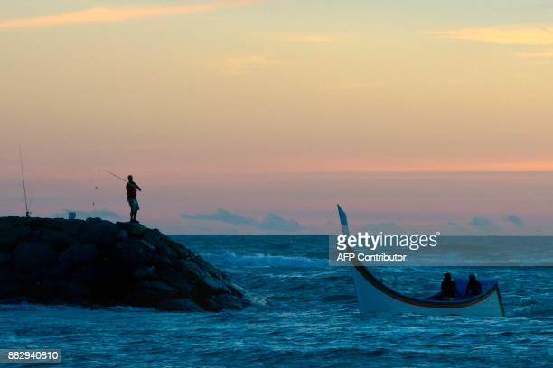This picture taken on October 18 2017 shows a man casting his fishing rod as a boat returns to shore at sunset on Lhoknga beach in Aceh Indonesias...