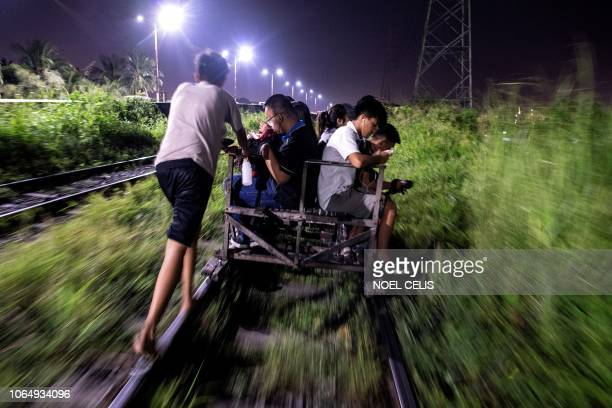 This picture taken on October 18 2018 shows a trolley boy pushing a homemade cart along a train track in Manila Scores of commuters in the city of...