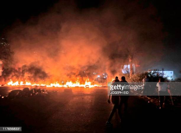 This picture taken on October 18 2019 shows burning tires set by protesters to block the main BeirutTripoli highway near the town of Tabarja north of...