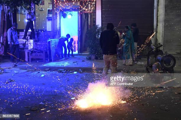 This picture taken on October 19 2017 shows Indian people using firecrackers celebrating Diwali Festival despite the ban imposed by the Supreme Court...