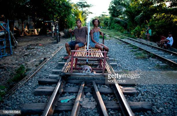 This picture taken on October 19 2018 shows trolley boy couple Tyson Aguha and Joan Acebo sitting along a train track waiting for passengers in...