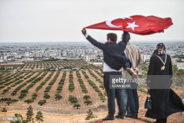 This picture taken on October 19, 2019 from the Turkish side of the border in Sanliurfa, Ceylanpinar district, shows members of 15 july martyrs...