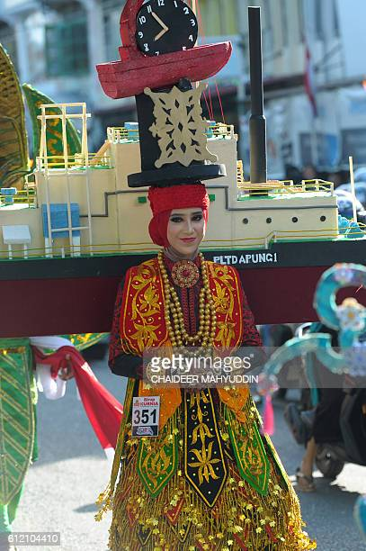 This picture taken on October 2 2016 shows an Acehnese model carrying a model copy of a ship destroyed during the 2004 tsunami and a clock displaying...