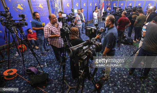 This picture taken on October 2 2018 shows Iraqi journalists performing interviews at the federal parliament headquarters in Iraq as the legislative...