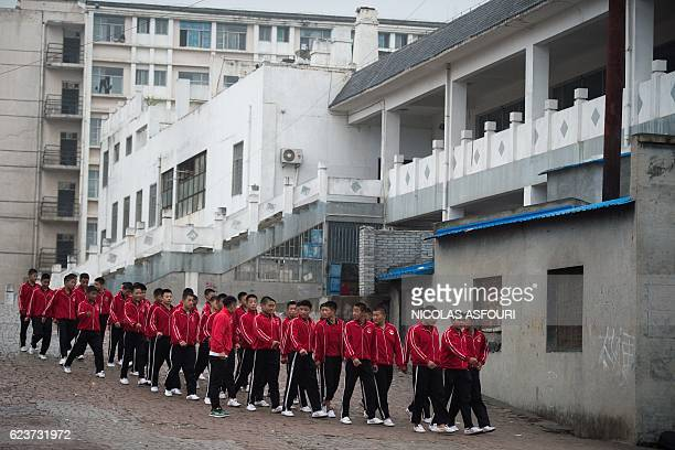 This picture taken on October 20 2016 shows students walking in formation from their dormitory to their daily practice of wushu at the Tagou martial...