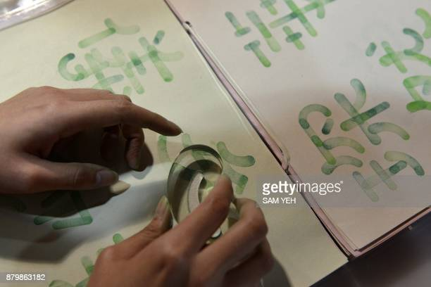 This picture taken on October 20 2017 shows a visitor testing a Chinese character with a stamp during an exhibition in Taipei Concerns in Taiwan are...