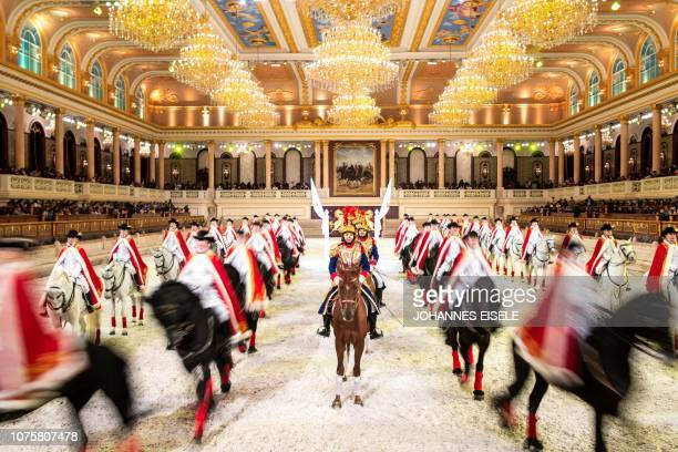 This picture taken on October 20 2018 shows Chinese riders and their horses taking part in a performance in the show hall of an equestrianthemed town...