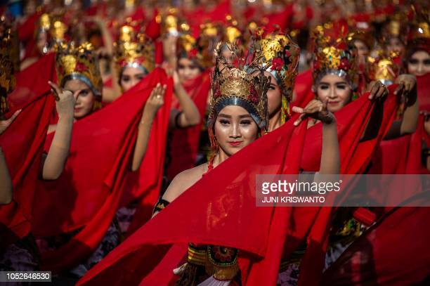TOPSHOT This picture taken on October 20 2018 shows traditional dancers performing the Gandrung Sewu dance at the festival on Boom beach in...