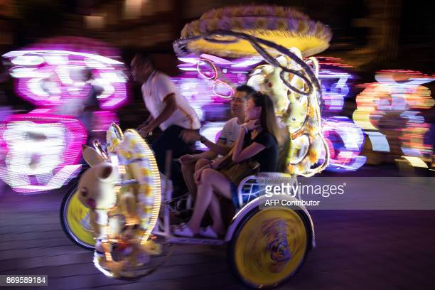 This picture taken on October 21 2017 shows a couple riding on a trishaw illuminated with LED lights and Pokemon character decorations on a street in...