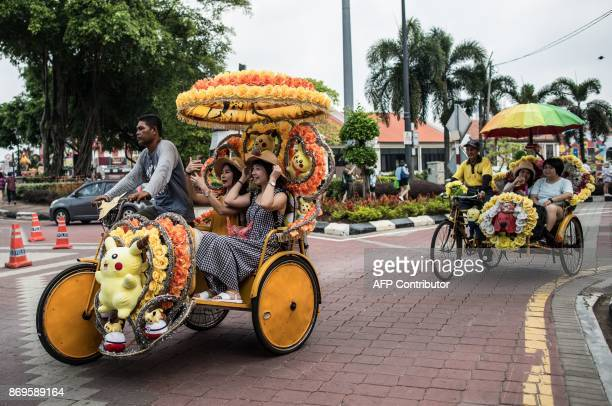 This picture taken on October 21 2017 shows tourists riding on trishaws with Pikachu and Angry Bird decorations on a street in Malaysia's historical...