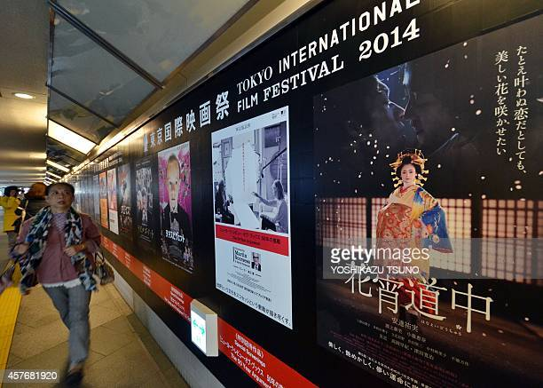 This picture taken on October 22, 2014 shows a pedestrian walking past posters of movies which will be screening at the Tokyo International Film...