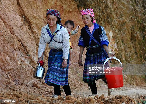 This picture taken on October 23 2012 shows a young ethnic Hmong hill tribe woman carrying a baby on her back as she makes way home in the...
