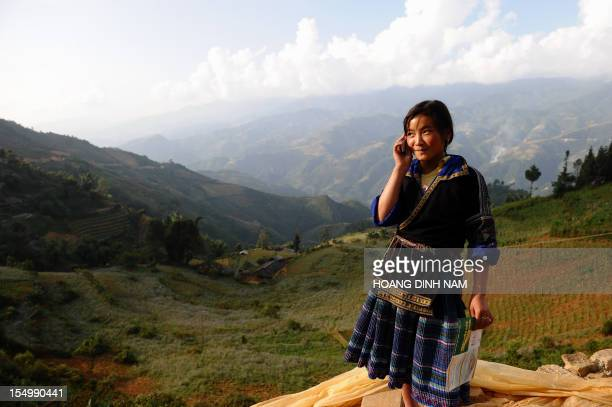 This picture taken on October 23 2012 shows an ethnic Hmong hill tribe girl talking on a cell phone on the flank of a hill in the mountainous...